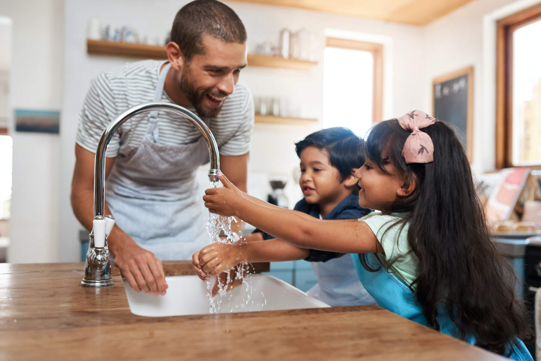 A father and children enjoy clean, filtered, softened water from the faucet.